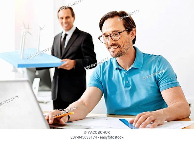 Inspired by work. Handsome young man sitting at the table and working on the laptop while his boss holding with a wind power station model in the background