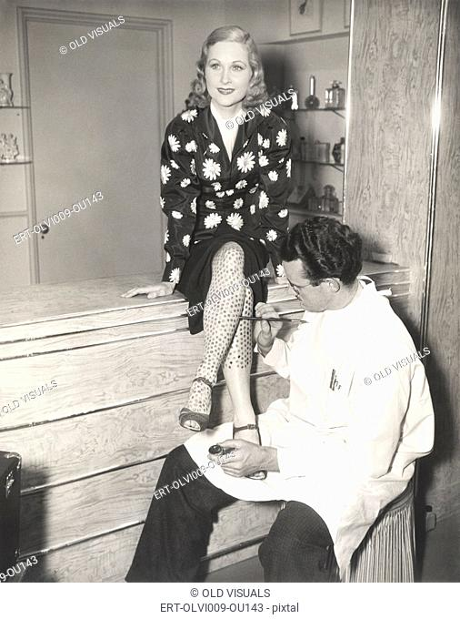 Makeup artist painting stockings on woman's legs