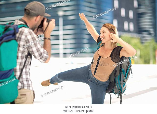 Man taking picture of posing girlfriend