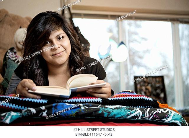 Hispanic student reading in dorm room