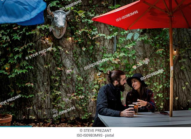 Young couple chatting in beer garden in evening, Brooklyn, New York, USA