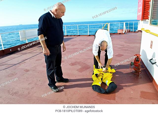 Marine pilots folding their safety suits minutes after arriving on a bulk carrier
