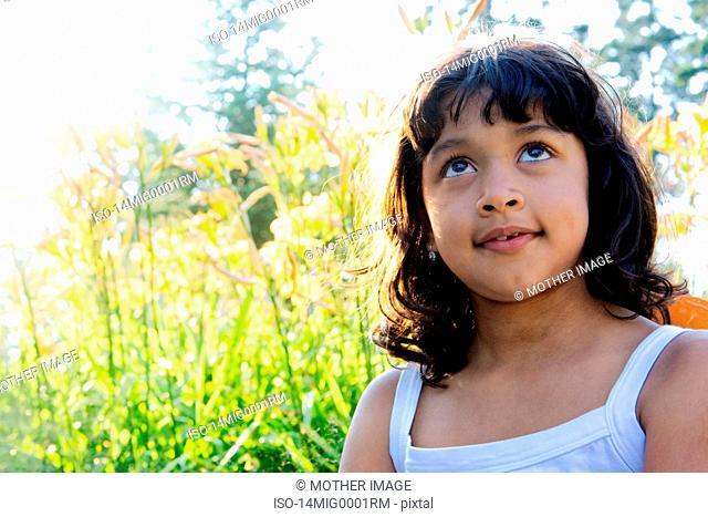 Hispanic girl day dreaming in garden