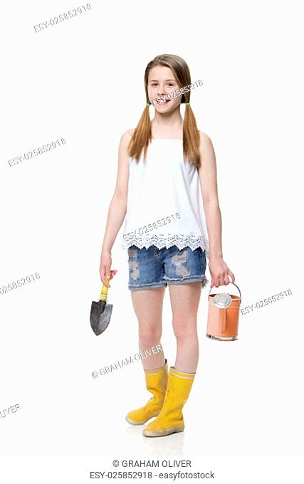 Young girl with a trowel and watering can dressed in casual clothing against a white background