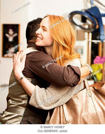 Male hairdresser hugging female customer in hair salon