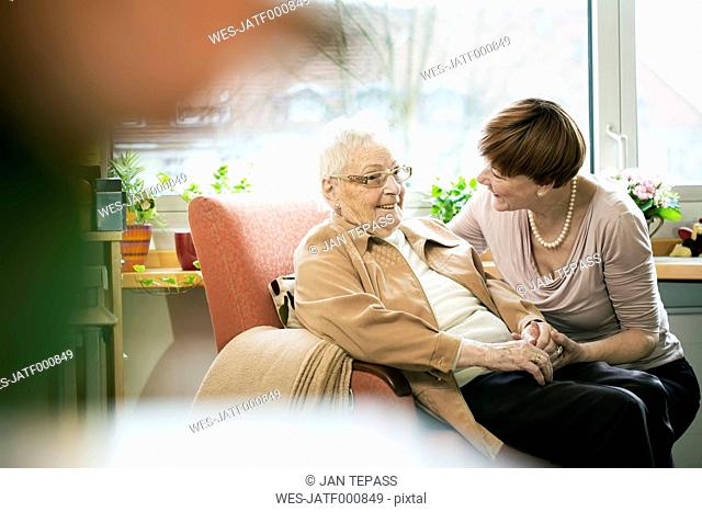 Adult daughter talking to her mother with Alzheimer's disease in her room at retirement home
