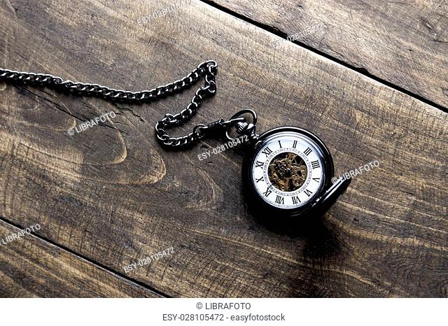 pocket watch on grunge wooden table, from above