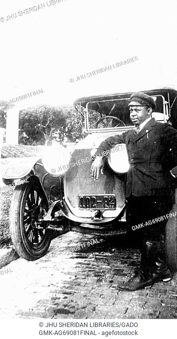 Full length portrait of an African American man leaning against headlights of a car, wearing chauffeur's uniform, neutral facial expression, 1919