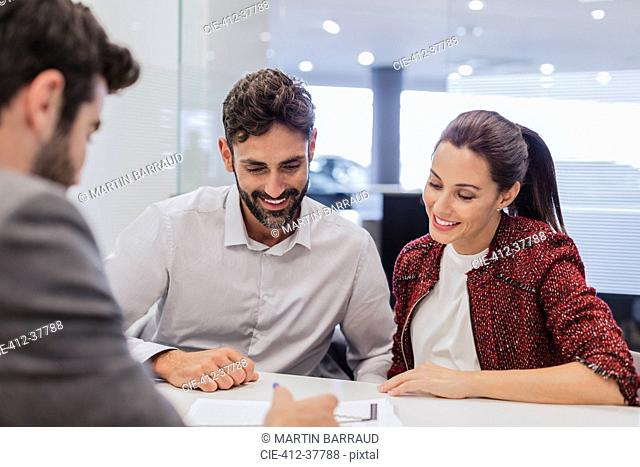 Car salesman explaining financial contract paperwork to couple customers in car dealership office