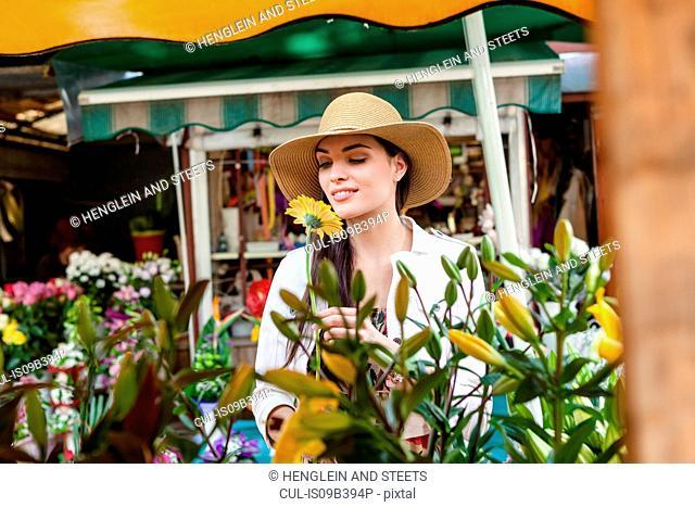 Young female tourist smelling flowers on market stall, Split, Dalmatia, Croatia
