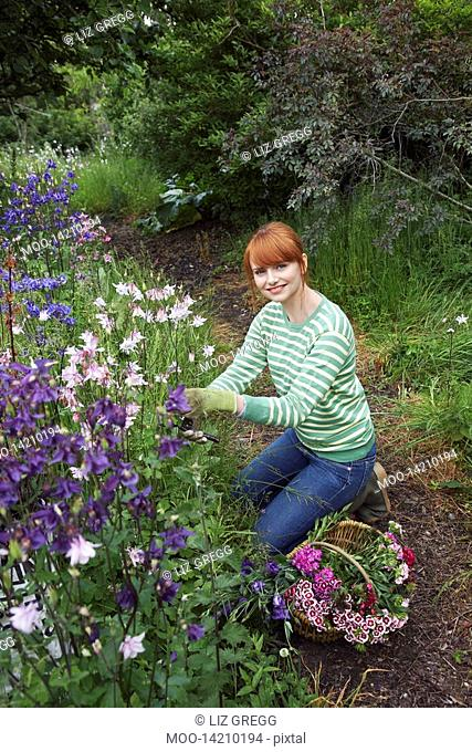Woman picking flowers in garden portrait