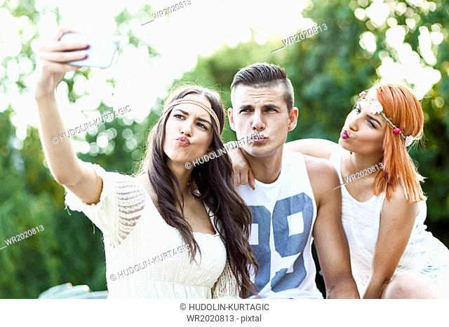 Young people in hippie style fashion taking self portrait