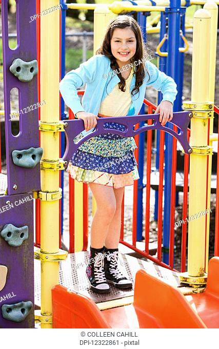 A young girl posing for the camera while playing at the playground; Oregon, United States of America