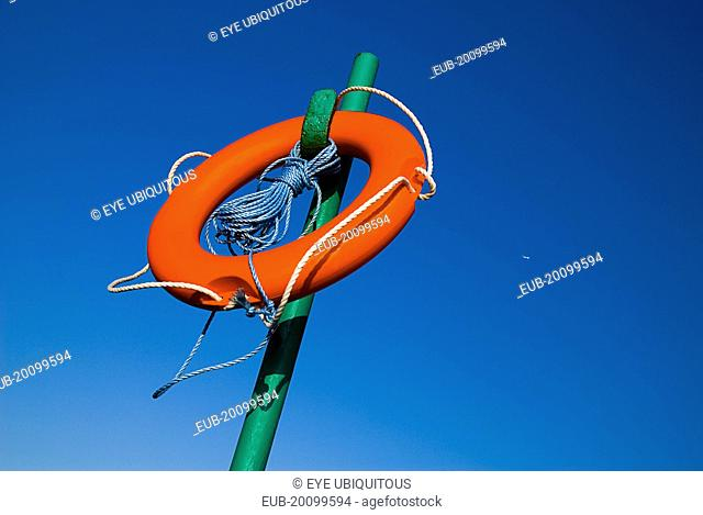 Red life belt on green stand with blue sky and plane behind