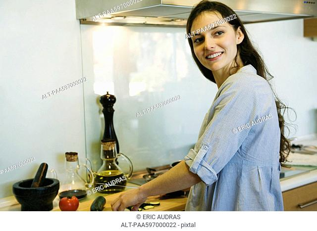 Woman cooking, smiling over shoulder, portrait