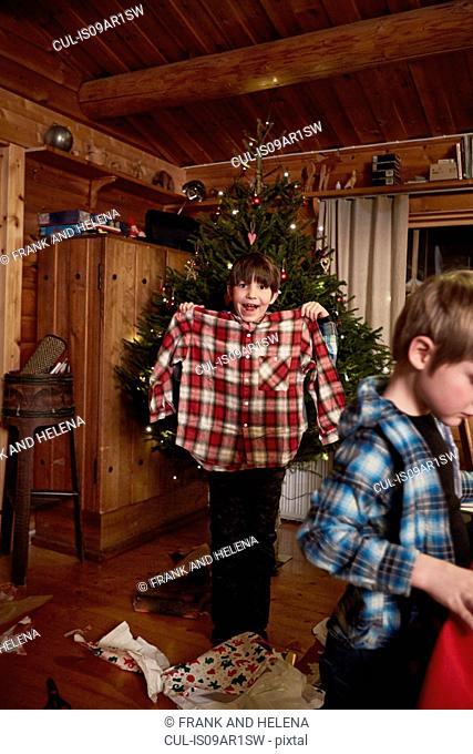 Joyful boy holding up Christmas shirt