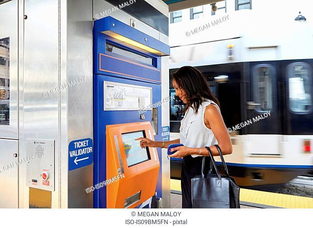 Businesswoman buying train ticket at machine