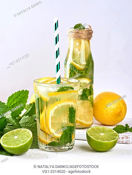 cold drink of fresh lemons, lime, mint green and pieces of ice in a glass on a white background and ingredients