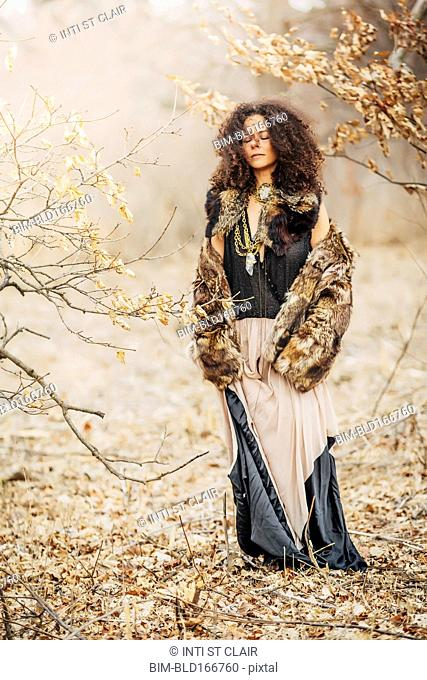 Mixed race woman wearing stylish clothes in field