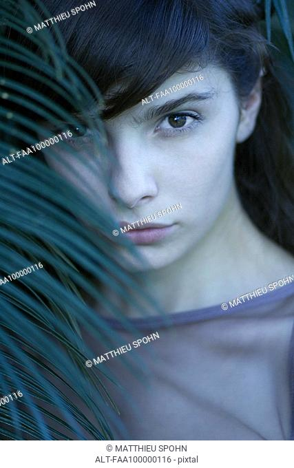 Young woman looking through palm leaf, portrait
