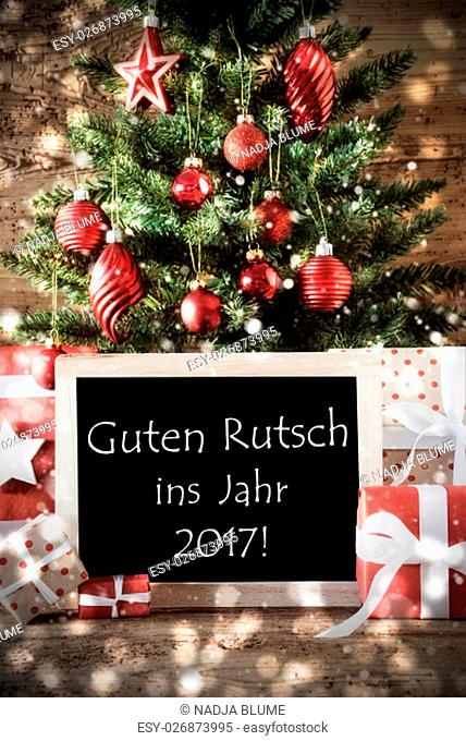 Christmas Tree With Balls And Snowflakes. Gifts Or Presents In The Front Of Wooden Background With Bokeh Effect. Chalkboard With German Text Guten Rutsch Ins...