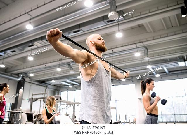 Young man exercising with fitness band in gym