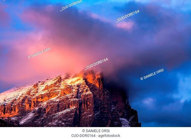 Alpenglow and clouds highlighting Tofana di Rozes, Cortina d'Ampezzo, Dolomites, Veneto, Italy