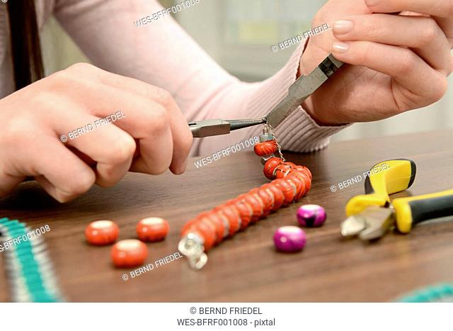 Young woman working on self-made bracelet