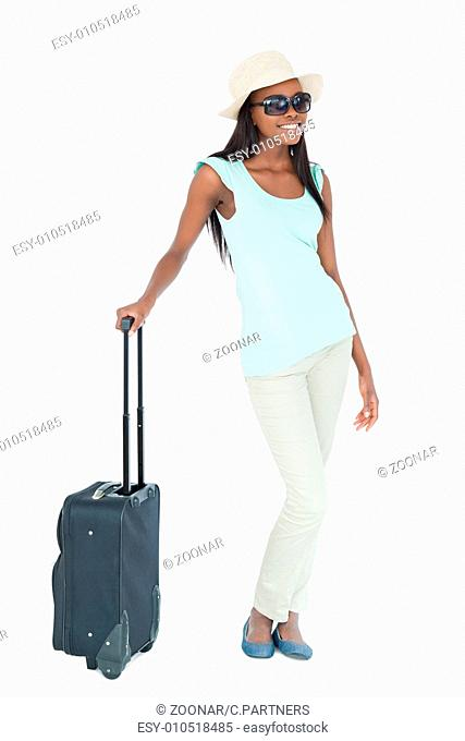 Young woman with sunglasses, hat and suitcase