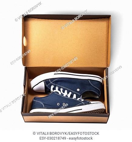Dark blue sports shoes inside cardboard box isolated on white background