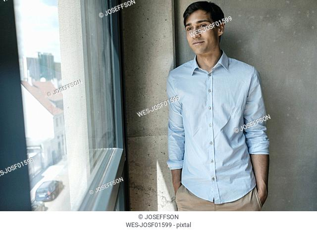 Smiling young man looking out of window