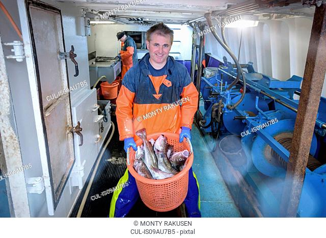 Fisherman with basket of fish on trawler, portrait