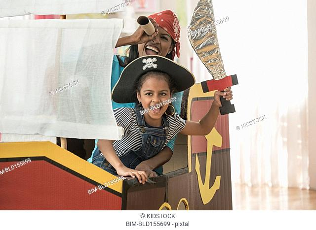 Hispanic mother and daughter playing pirate in bedroom