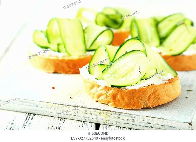 Tasty fresh bruschetta with cucumber on cutting board on white wooden background
