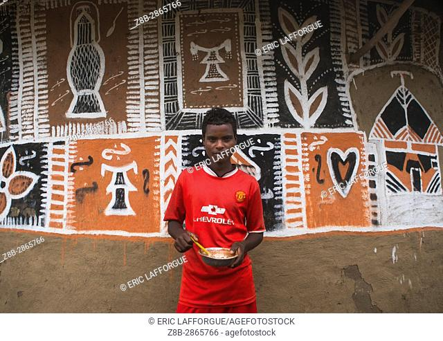 Young man painting the wall of a traditional ethiopian house, Kembata, Alaba Kuito, Ethiopia