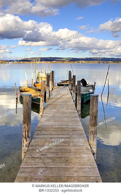 Fishing pier with fishing boats on the shore of Iznang with a view to Radolfzell, Landkreis Konstanz county, Baden-Wuerttemberg, Germany, Europe