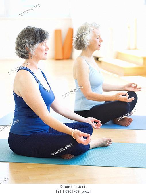 Two senior women practicing yoga
