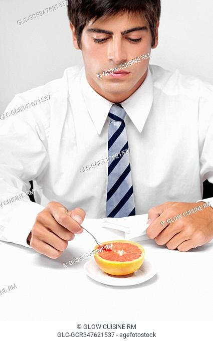 Close-up of a businessman eating a grapefruit with a spoon