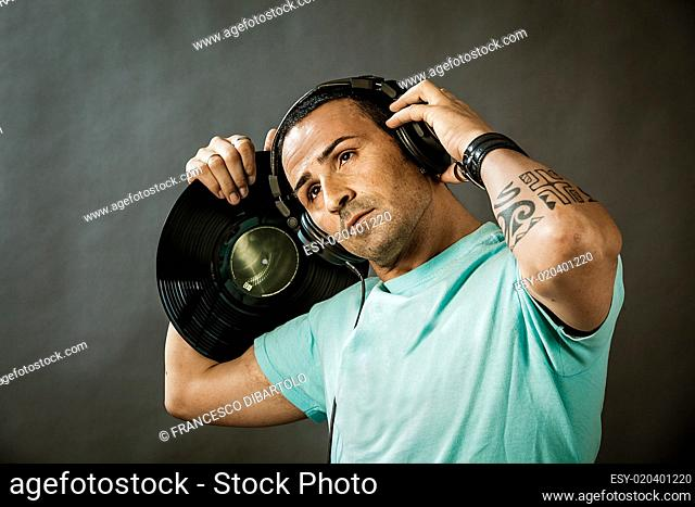 Man with blue shirt and vinyl in his hands