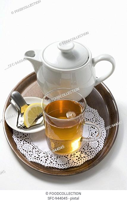 A serving of black tea with lemon