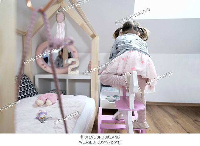 Toddler girl climbing on rocking horse in nursery