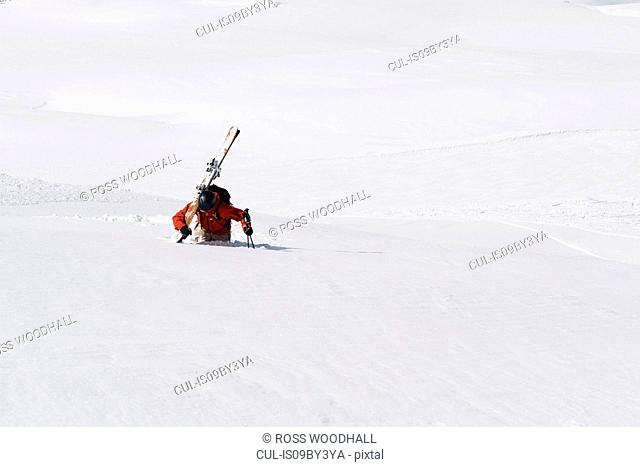Male skier trudging up mountain through deep snow, Alpe-d'Huez, Rhone-Alpes, France