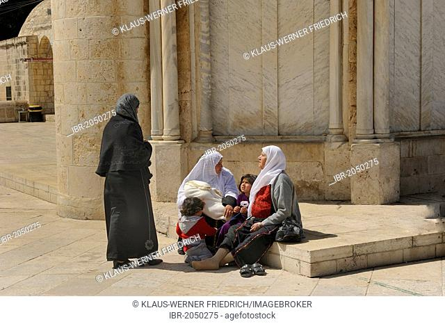 Israeli Palestinian women wearing headscarves resting with their children on the base of the Ascension Church, Temple Mount, Muslim Quarter, Old City, Jerusalem