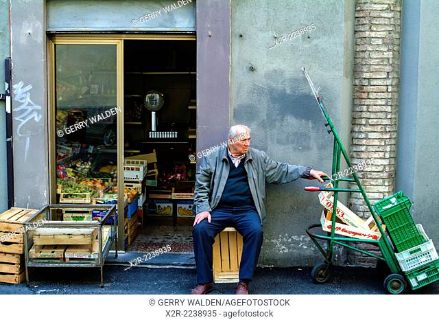 Elderly man sitting on a box outside a greengrocery shop (Perugia, Umbria)