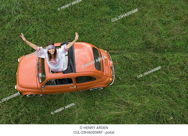 Hippy female stretching out of car