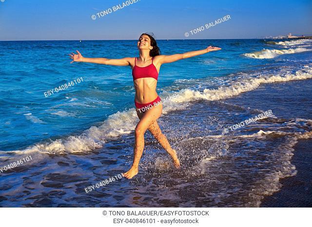 Bikini girl running to the beach shore water of Mediterranean sea