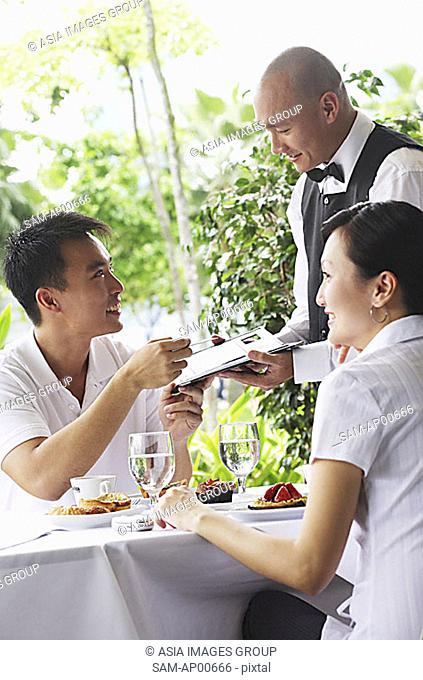 Couple in restaurant, making payment to waiter