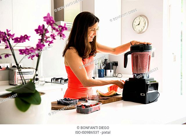 Woman preparing smoothie in blender