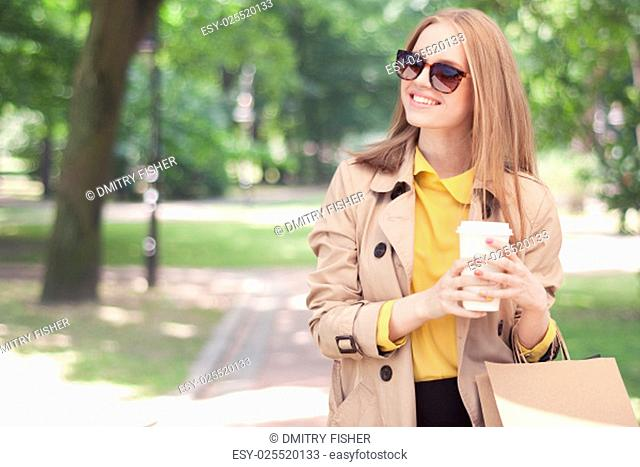Young fashionable woman taking a coffee break after shopping, walking with a coffee-to-go in her hands against green city park background