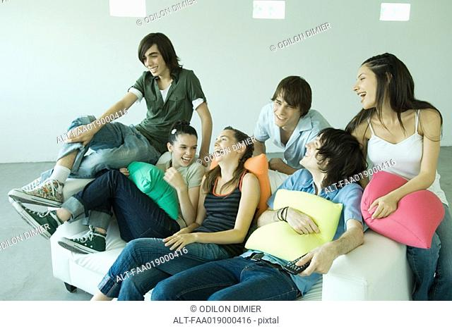Group of young friends sitting on sofa, laughing